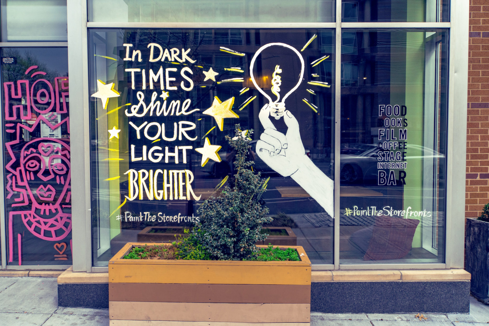 "window at busboys and poets in washington reads ""in dark times, shine your light brighter"""